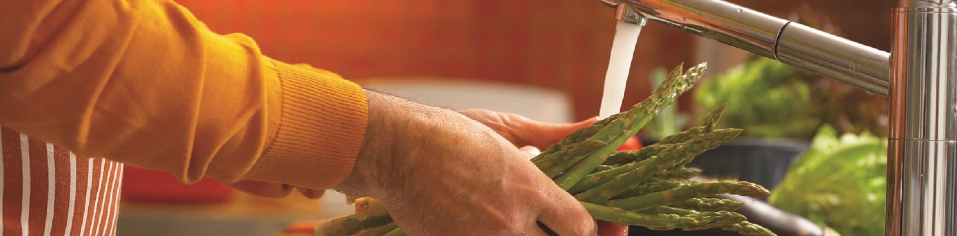 homeowner washes vegetables under kitchen tap